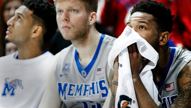 Dejected University of Memphis guard Markel Crawford (right) watches from the bench with teammates Christian Kessee (left) and Chad Rykhoek (middle) during a 103-62 drubbing by No. 19 Southern Methodist at Moody Coliseum in Dallas on Saturday, March 4, 2017. It was the worst loss the Tigers have suffered since 1947.