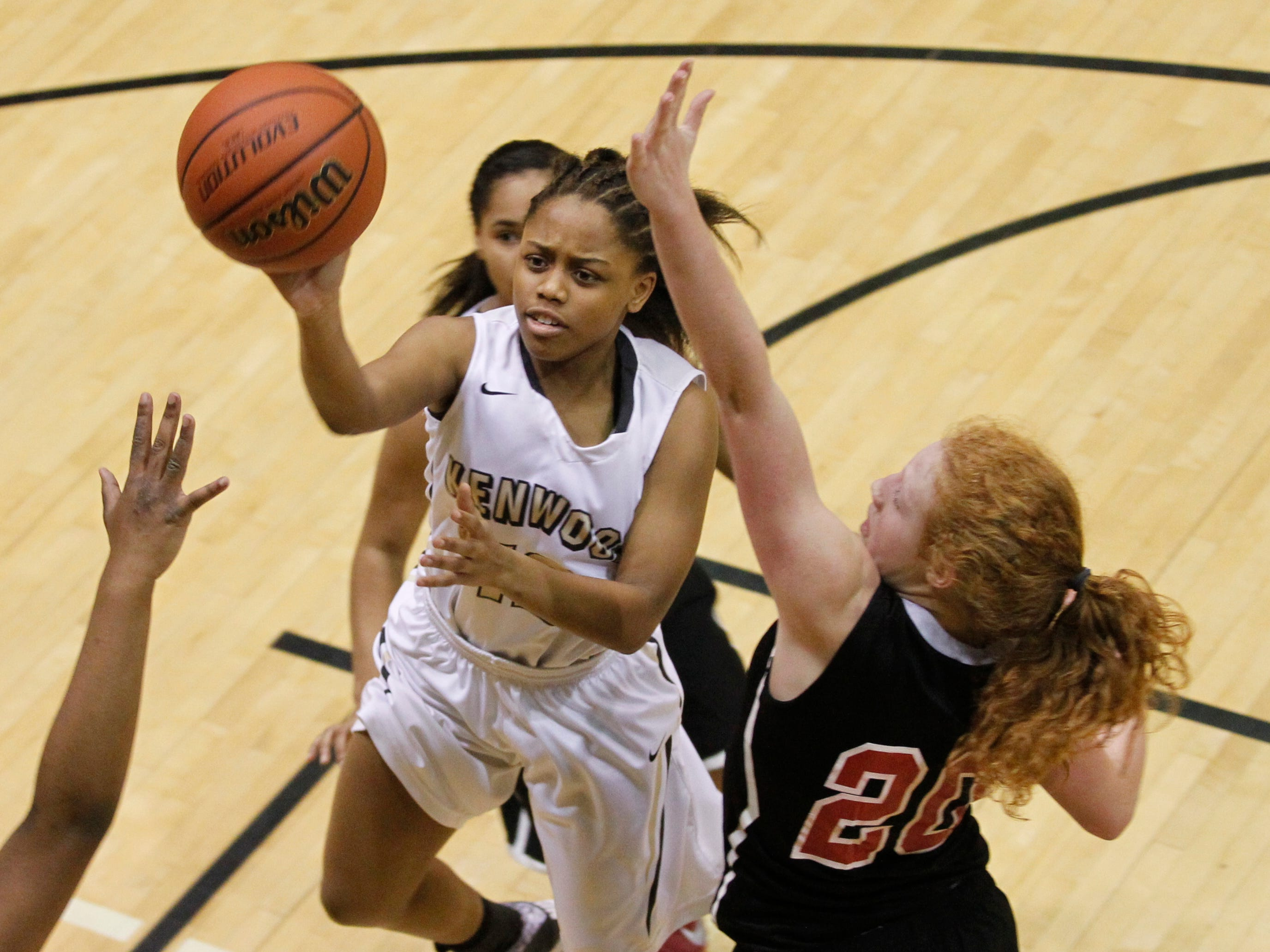 Kenwood's Malia Umrani shoots around Rossview's Haylee Croom during Friday night's District 10-AAA action at Kenwood.