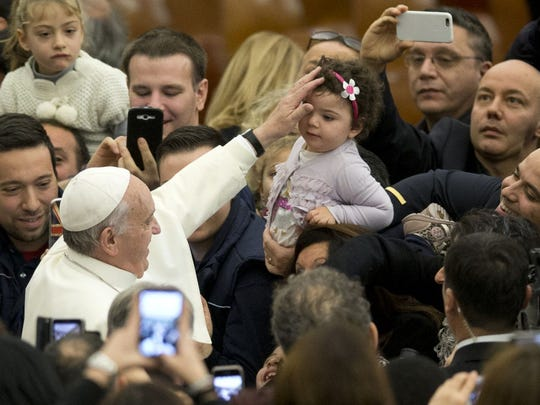 Pope Francis blesses a baby during an audience with the Holy See's employees in the Paul VI hall at the Vatican on Monday.