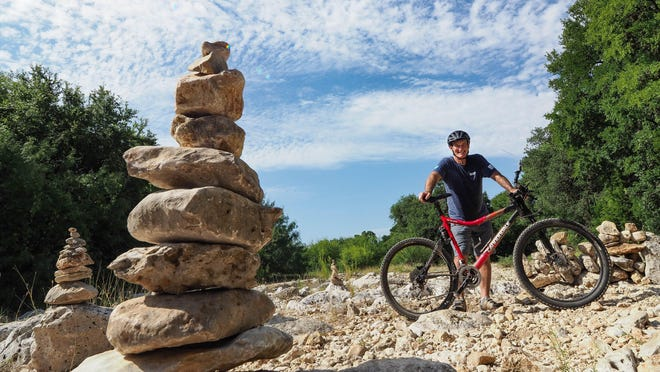 Erich Schlegel poses with his mountain bike on a trail at Purgatory Creek Natural Area in San Marcos.
