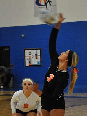 Garden City's Heather Pennington returns the ball as teammate Jacey Law looks on.