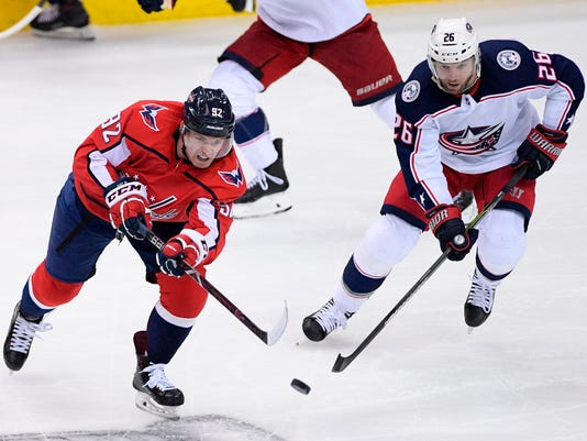 Washington Capitals center Evgeny Kuznetsov (92), of Russia, passes the puck against Columbus Blue Jackets left wing Thomas Vanek (26), of Austria, during the third period in Game 1 of an NHL first-round hockey playoff series Thursday, April 12, 2018, in Washington. The Blue Jackets won 4-3 in overtime. (AP Photo/Nick Wass)