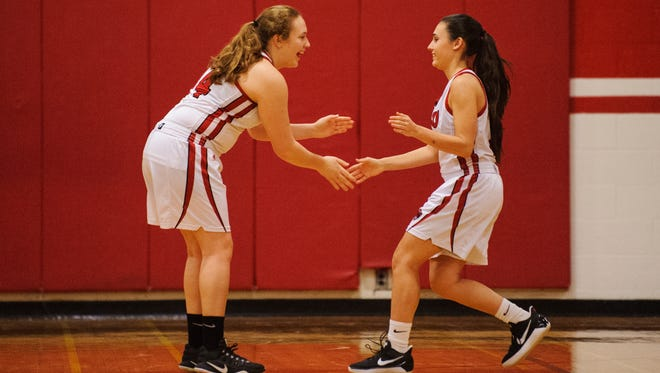 CVU's Julia Neeld (14) greets Nicole Eaton (2) during player introductions in the girls basketball game between the St. Johnsbury Hilltoppers and the Champlain Valley Union Redhawks at CVU High School on Tuesday night January 9, 2018 in Hinesburg.