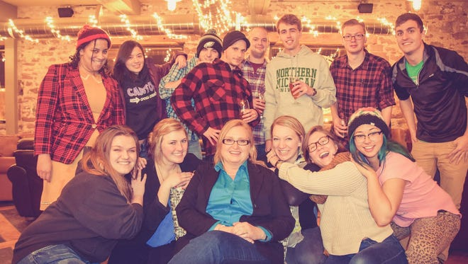 Cheryl Reed, center, relaxes with the staff of the Northern Michigan University student newspaper at its Christmas party.