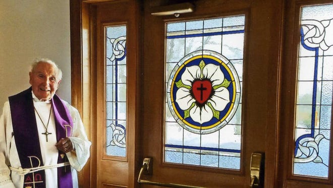 Pastor Patrick Kelly stands near the new stained glass window at Saint John's Lutheran Church. The window was created byBill Vidonish Studios in Lexington.