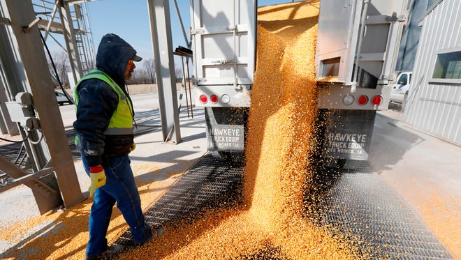 Phil Conklin unloads corn from a truck at the Heartland Co-op, Thursday, April 5, 2018, in Redfield, Iowa.