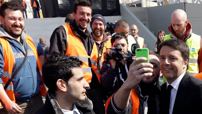 Italian Premier Matteo Renzi, right, takes a selfie with a worker on the occasion of his visit at the Expo site in Rho, near Milan, Italy, in March.