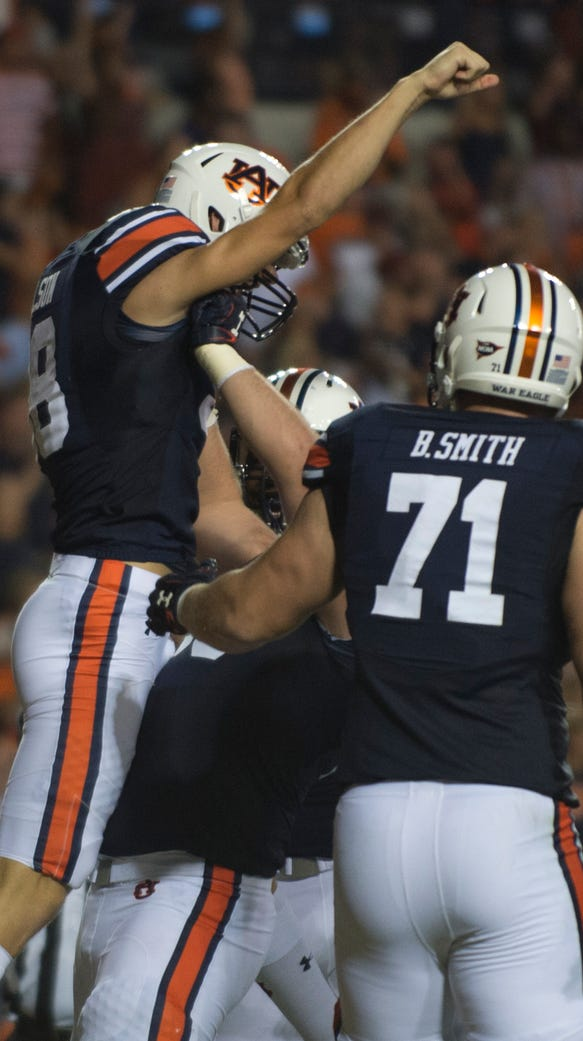 Auburn offensive lineman Mike Horton (64) lifts up