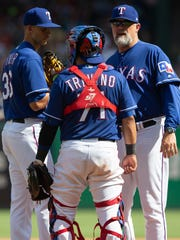 Texas Rangers starting pitcher Mike Minor (36), catcher Jose Trevino (71), and pitching coach Doug Brocail (46) meet on the mound during the seventh inning of a baseball game against the Colorado Rockies, Saturday, June 16, 2018, in Arlington, Texas. (AP Photo/Sam Hodde)
