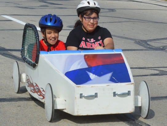 A rider in a Super Kids soap box racer is all smiles