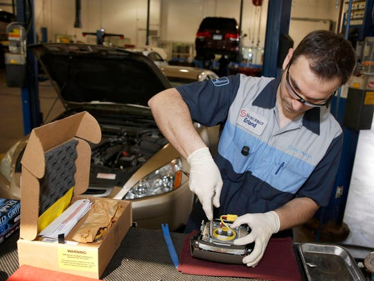 Erland Zeka installs a new air bag inflators as he performs the Takata service recall on a 2005 Honda Accord LX at Suburban Honda in Farmington Hills in May 2015.