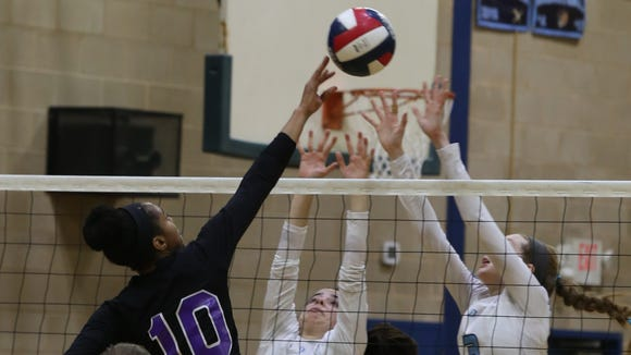 New Rochelle's Rachel Darius (10) tips the ball with Ursuline's Annie Conlon (7) and Katie McLoughlin (3) at the net during Section 1 Class AA volleyball semifinals at Ursuline School in New Rochelle Nov. 2, 2016.  Ursuline defeats New Rochelle with a 25-19 fourth-set win.