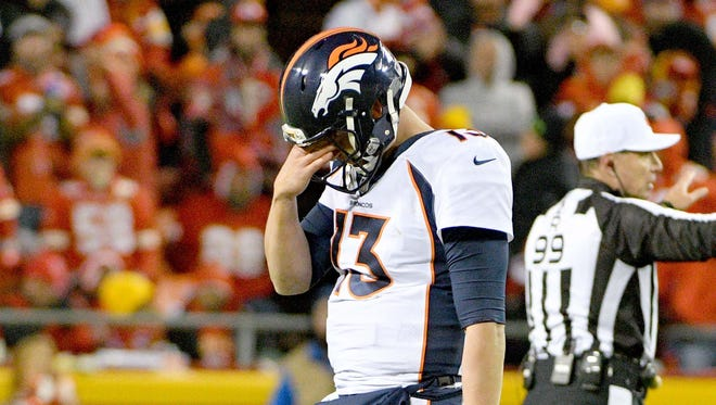 Denver Broncos quarterback Trevor Siemian (13) walks to the sidelines after calling time out during the second half against the Kansas City Chiefs at Arrowhead Stadium.