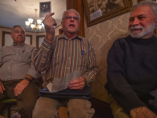 Ed Ingels, left, and Mike Pecotte, right, listen Wayne Bartholow, center, as he holds a photo and talks about his Christmas memories during the Historical Holiday Chat inside Waynesboro's Historical Society's Oller House on Saturday, Dec. 12, 2015, in Waynesboro, Pa. Bartholow also brought a letter that he had written when he was six years old to Santa Clause.