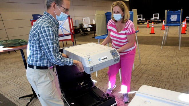 Mark Minion and Sherry Yocum unload voting machines at the LeGrand Center on Wednesday.