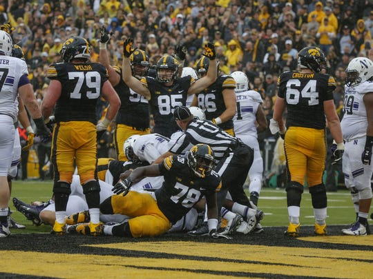 Iowa running back LeShun Daniels, Jr., crosses the goal line against Northwestern, as linemen Sean Welsh (79), James Daniels (78) and Cole Croston (64) look on. Iowa has rushed for 17 touchdowns this season.