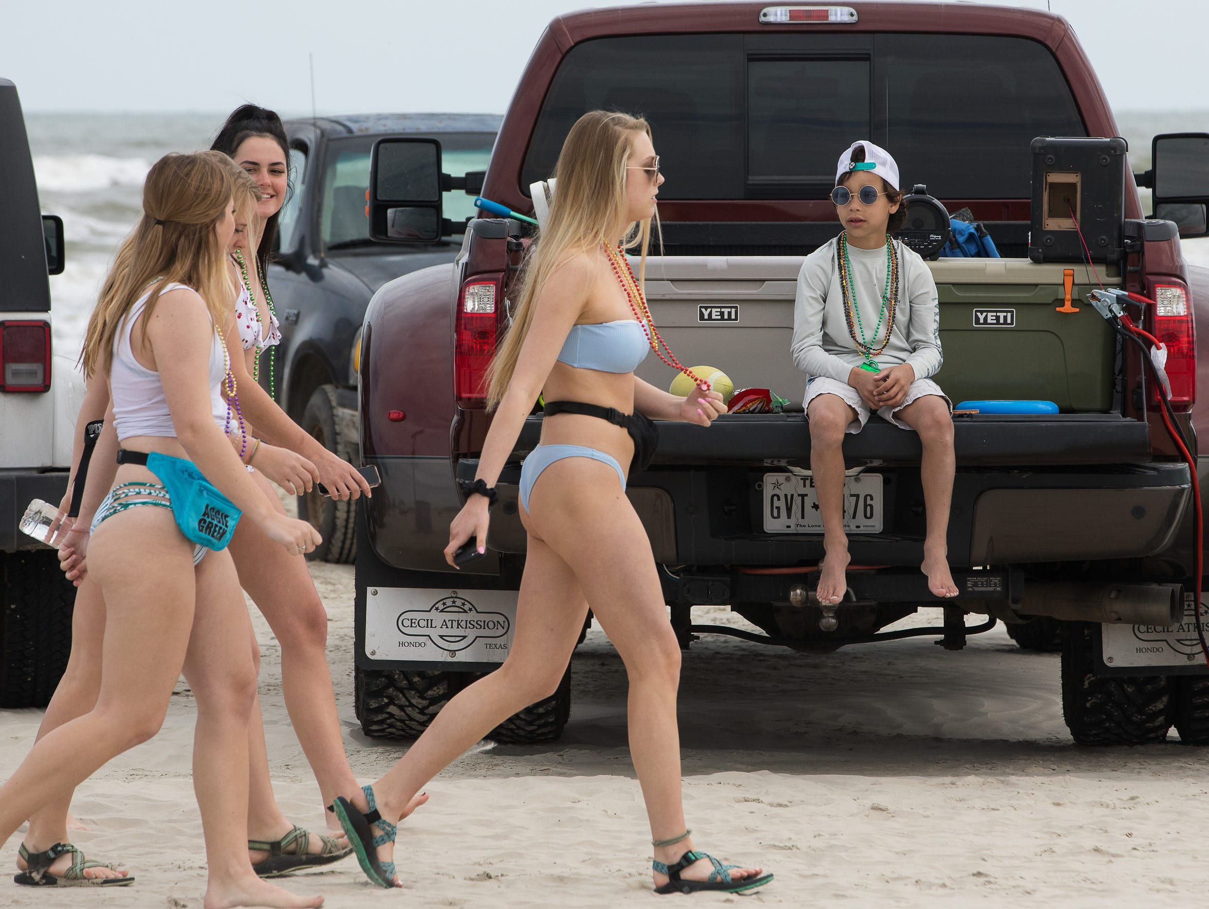 A group of spring breakers walk past a young boy sitting on the bed of a pickup truck on Port Aransas' beach in March.