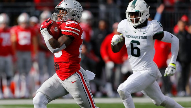 Ohio State tailback Mike Weber sets sail on an 82-yard touchdown run in the second quarter of Saturday's win over Michigan State.