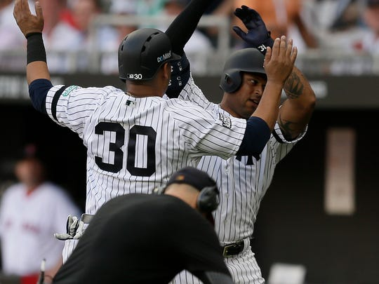 New York Yankees' Aaron Hicks, right, celebrates after hitting a home run against the Boston Red Sox during the first inning of a baseball game, Saturday, June 29, 2019, in London. Major League Baseball made its European debut game today at London Stadium. (AP Photo/Tim Ireland)