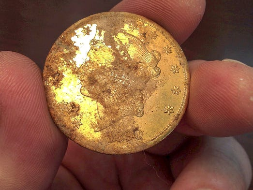 An 1890 gold coin, part of a collection of coins found buried on private property, is displayed on Feb. 25 in Tiburon, Calif. A couple stumbled onto a cache of gold coins worth $10 million buried in their back yard while walking with their dog on their property in 2013. The coins will go on sale on May 27.