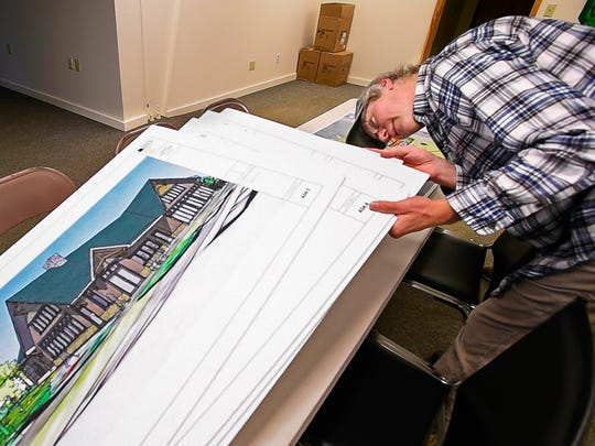 Sean Lawson of Lawson's Finest Liquids looks through architectural plans for his planned expansion into a two-building facility in Waitsfield on Tuesday, May 2, 2017.