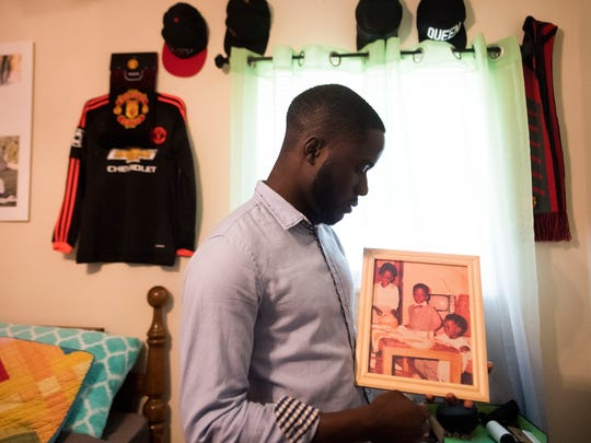Timothy Brass holds a photo from his childhood, which