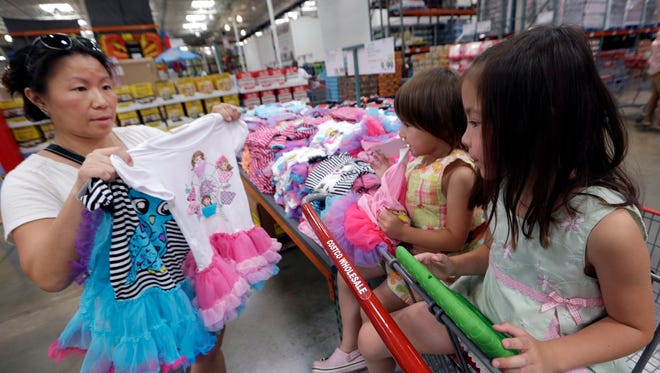 Carry Johnson, left, shows dresses to her daughters Zoey, 3, center, and Payton while they shop at a Costco in Plano, Texas.