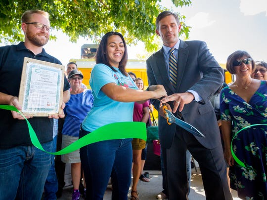 Kristen Aguilar, food planning and policy specialist for the La Semilla Food Center, cuts a ribbon with U.S. Sen. Martin Heinrich, D-N.M., to launch the Farm Fresh Mobile Market at Klein Park, Wednesday, August 24, 2016.
