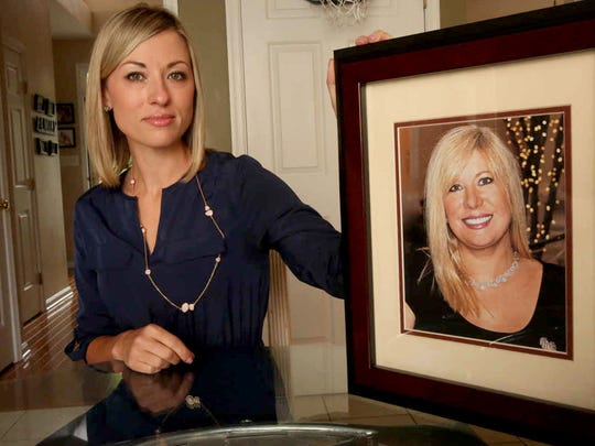In this May 25, 2016, photo, Kim Pack poses with a photo of her late mother, talk-show host April Kauffman, in Linwood.