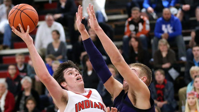 Holy Cross' Tyler Bezold drives to the basket against Campbell County's Garren Bertsch. Bezold ended up with 14 points in the Indians' 69-42 victory.