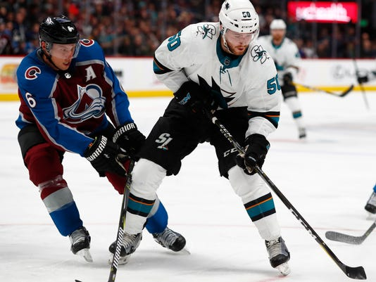 Colorado Avalanche defenseman Erik Johnson, left, swings at the puck as San Jose Sharks center Chris Tierney looks to take a shot in the second period of an NHL hockey game Tuesday, Feb. 6, 2018, in Denver. (AP Photo/David Zalubowski)