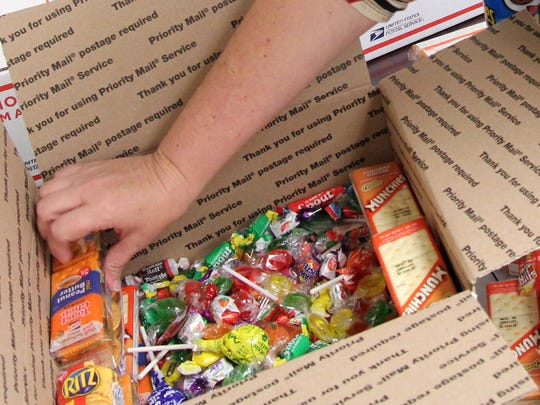 Tassy Mannis carefully arranges crackers and candies to send overseas to sailors.