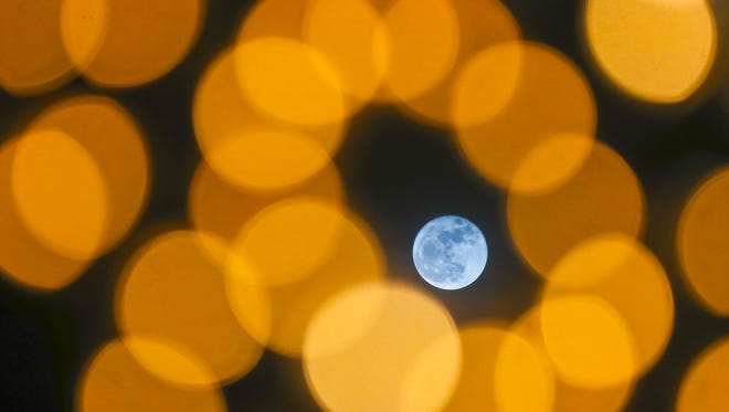 The super moon shines through holiday lights in Jeffersonville Dec. 3, 2017.  A supermoon is a new or full moon closely coinciding with perigee Ð the moon's closest point to Earth in its monthly orbit.