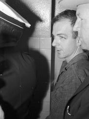Lee Harvey Oswald in police custody in Dallas, following