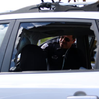 A Fort Myers police officer looks inside a car that