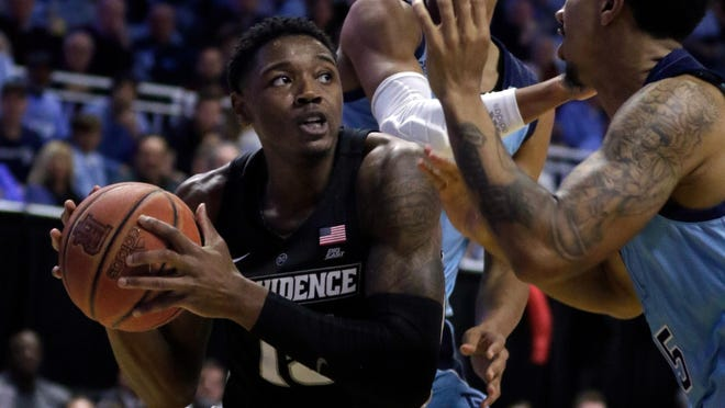 URI's Jacob Toppin, center, and Mekhi Long, right, defend against the Friars' Emmitt Holt in their 2019 matchup at the Ryan Center.  The 2020 game between the state rivals has been canceled.