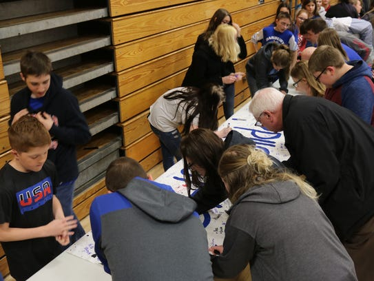"""Danbury students and staff sign a poster with """"#DHSSolidarity"""""""