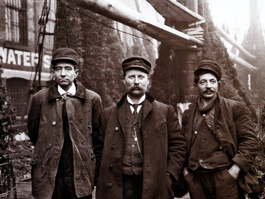 Rouse Simmons (better known as The Christmas Tree Ship) Captain Herman Schuenemann, center, stands with his Christmas trees, along with L. Vanaman, left and Mr. Colberg. Courtesy of Manitowoc County Historical Society