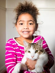Essence Bagley, 5, holds her cat in her Walnut Hills