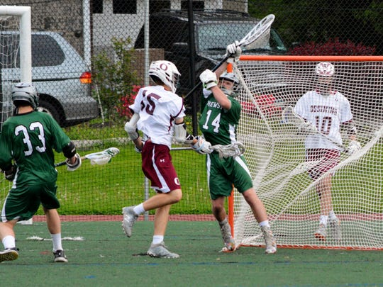 Ossining's John Turnquist scores past Brewster goalie Billy Finn in the first quarter of a Section 1 Class B playoff game.