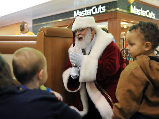 Santa Claus sings Christmas carols to Alana Huizenga and her 1-year-old son Harper, of Zanesville, and Kaiden Wallace, 2, of Cambridge, at a children's recreation area in the Colony Square Mall. Jan Smith has portrayed Santa Claus at various venues for 25 years.