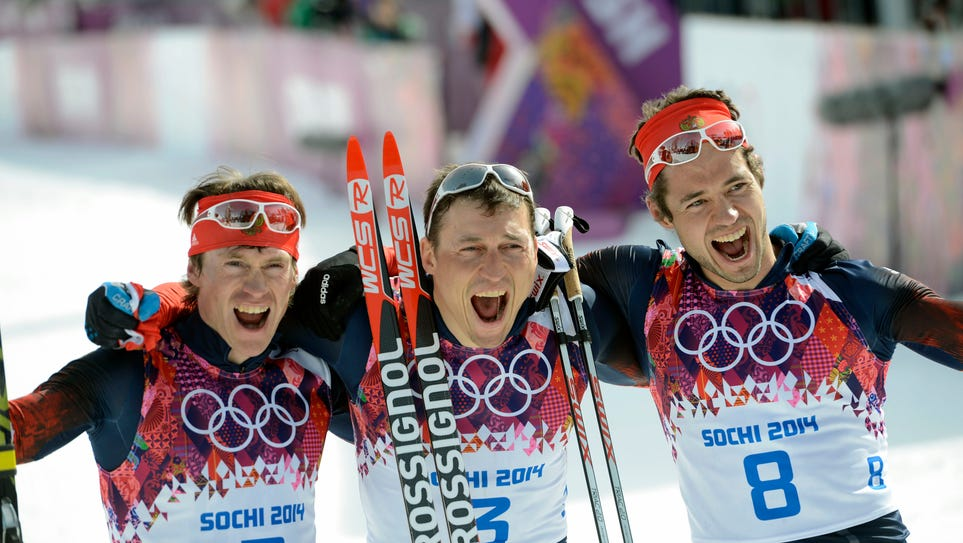 Feb 23, 2014; Krasnaya Polyana, RUSSIA;  Alexander Legkov (gold) (center), Maxim Vylegzhanin (silver) (left) and Ilia Chernousov (bronze) (right)  all from Russia celebrate on the podium as they swept the medals in the men's cross-country 50k mass start during the Sochi 2014 Olympic Winter Games at Laura Cross-Country Ski and Biathlon Center. Mandatory Credit: Jack Gruber-USA TODAY Sports