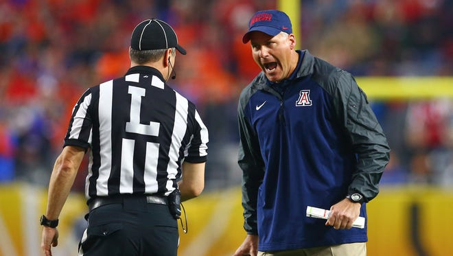 Arizona Wildcats head coach Rich Rodriguez (right) argues with a referee in the second quarter against the Boise State Broncos in the 2014 Fiesta Bowl at University of Phoenix Stadium in Glendale on Dec. 31.