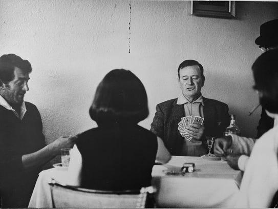 John Wayne and wife Pilar playing cards with Dean Martin