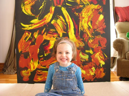 """Marla Olmstead in front of a big orange and yellow painting. From """"My Kid Could Paint That."""""""