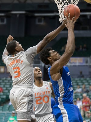 Miami forward Dewan Huell (20) looks on as his teammate guard Anthony Lawrence II (3) attempts to block the shot of Middle Tennessee forward Brandon Walters, right, in the first half of an NCAA college basketball game at the Diamond Head Classic, Monday, Dec. 25, 2017, in Honolulu.