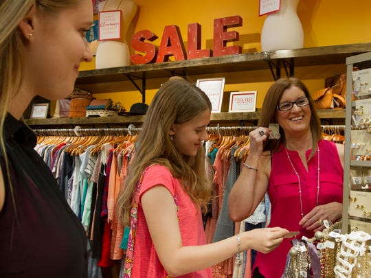 Rachel Norton and her daughters Claire, 16, and Jillian, 12, check out some of the goods from Francesca's at a brief shopping trip to Bell Tower Shops in Fort Myers Wednesday afternoon. Norton, of Lehigh Acres, can walk with her daughters around malls with no pain after having had a procedure done call VenusSeal.