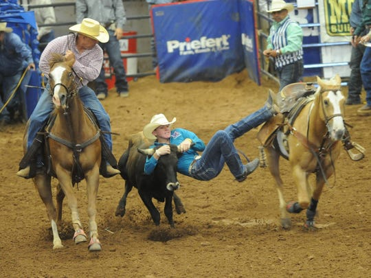 Clyde's Dalton Walker competes in the steer wrestling competition during the second go-round Thursday, June 8, 2017 at the Texas High School Rodeo Association's State Finals at the Taylor County Coliseum. Walker's hazer, Matt Reeves, looks on to the left of Walker.