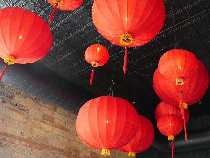 Red lanterns are suspended from the ceiling in the