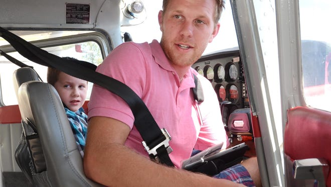 Evan Harper, 7, gets ready for a small plane ride on Aug. 12 out of Oakland Southwest Airport in New Hudson. His flight instructor, Nate Pedersen, prepares to take up the single engine airplane.
